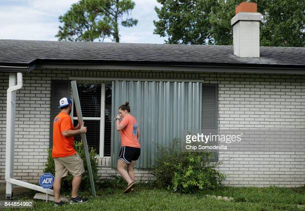 Caleb Rich and his wife Rachel Rich put metal shutters over windows on their home ahead of the arrival of Hurricane Irma September 9 2017 in Daytona...