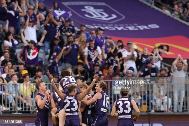 Caleb Serong of the Dockers celebrates a goal with team mates during the round 22 AFL match between the Fremantle Dockers and West Coast Eagles at...