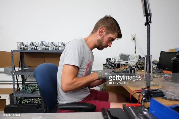 Caleb Tapp works on a motor assembly for a Ghost Gunner milling machine at the Defense Distributed factory in Austin Texas on August 1 2018 The US...