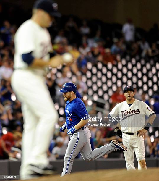 Caleb Thielbar and Trevor Plouffe of the Minnesota Twins look on as Adam Lind of the Toronto Blue Jays rounds the bases after hitting a threerun home...