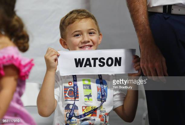 Caleb Watson, son of Bubba Watson of the United States, holds his father's nameplate after the final round of the Travelers Championship at TPC River...