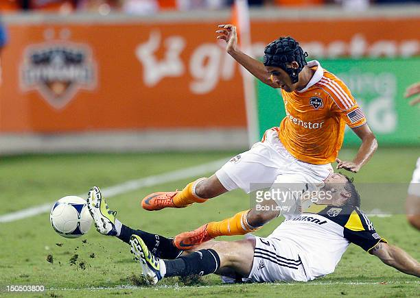 Calen Carr of the Houston Dynamo is tackled by Danny O'Rourke of the Columbus Crew at BBVA Compass Stadium on August 19 2012 in Houston Texas