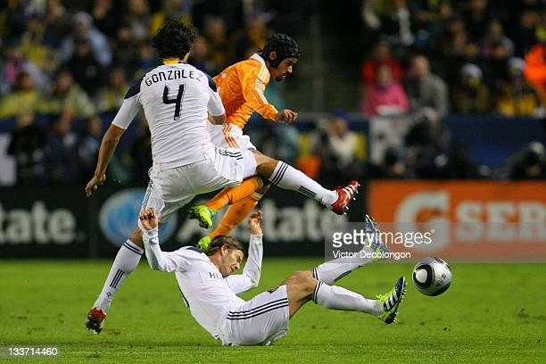 Calen Carr of the Houston Dynamo jumps over David Beckham of the Los Angeles Galaxy during the 2011 MLS Cup at The Home Depot Center on November 20...