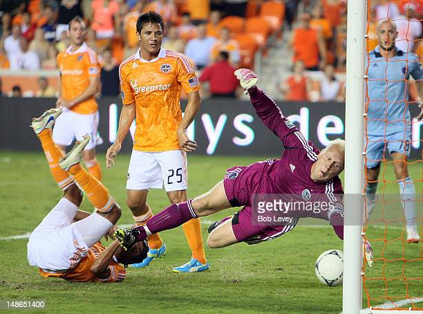 Calen Carr of the Houston Dynamo slips one past goalkeeper Jimmy Nielsen of the Sporting KC for a goal as Brian Ching of the Houston Dynamo looks on...