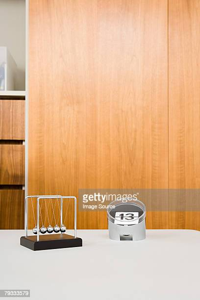a calendar and a newtons cradle on a desk - desk toy stock photos and pictures