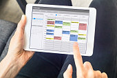 Calendar app on tablet computer with planning of the week with appointments, events, tasks, and meeting. Hands holding device, time management concept, organization of working hours planner, schedule