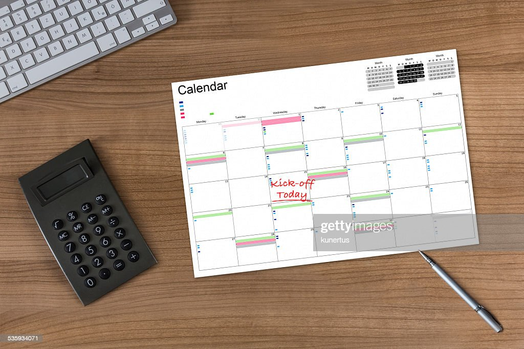 Calendar Kick-off and Calculator on wooden Table : Stock Photo