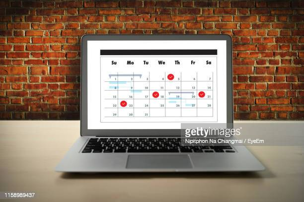 calendar over laptop screen against wall - instrument of time stock pictures, royalty-free photos & images