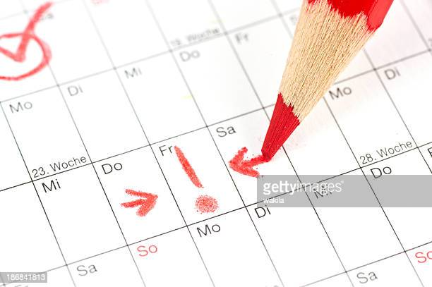 calender - ausrufezeichen bei termin am freitag mit rotem stift - time management stock photos and pictures