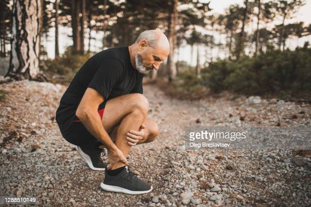 calf muscle injury on running outdoors. senior man holding knee by hands and suffering with pain. sprain ligament or periosteum problem. - old man feet stock pictures, royalty-free photos & images