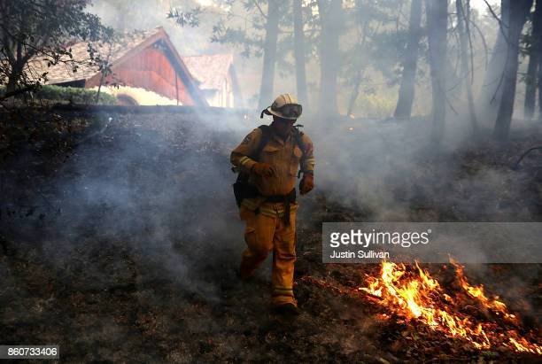 CalFire chief runs past burning grass during a firing operation while battling the Tubbs Fire on October 12 2017 near Calistoga California At least...