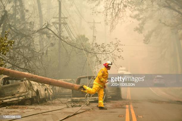 CalFire firefighter Scott Wit steps over a downed power line as he surveys abandoned burned cars on the side of the road after the Camp fire tore...