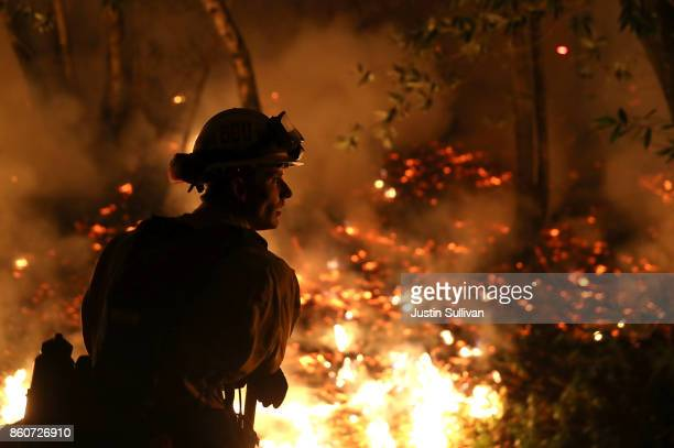 CalFire firefighter Trevor Smith monitors a firing operation while battling the Tubbs Fire on October 12 2017 near Calistoga California At least...