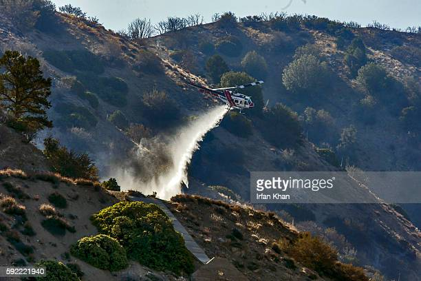 CalFire helicopter makes a water drop on still smoldering remnants of Blue Cut Fire on the hilltop ridges along Hwy 2 in Wrightwood