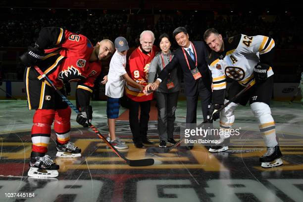 Calgary Flames alumni Lanny McDonald drops the ceremonial puck with David Backes of the Boston Bruins and Mark Giordano of the Calgary Flames at the...