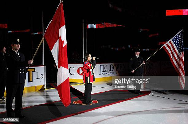 Calgary Flames anthem singer Heather Liscano sings the Canadian national anthem flanked by members of the Calgary Fire Department before the game...