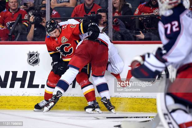 Calgary Flames Center Mikael Backlund and Columbus Blue Jackets Right Wing Josh Anderson rough one another in the corner during the third period of...