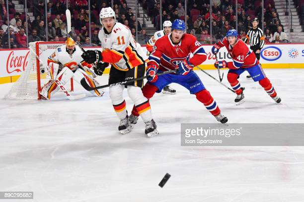 Calgary Flames Center Mikael Backlund shoots the puck awayfrom Montreal Canadiens Center Byron Froese during the Calgary Flames versus the Montreal...