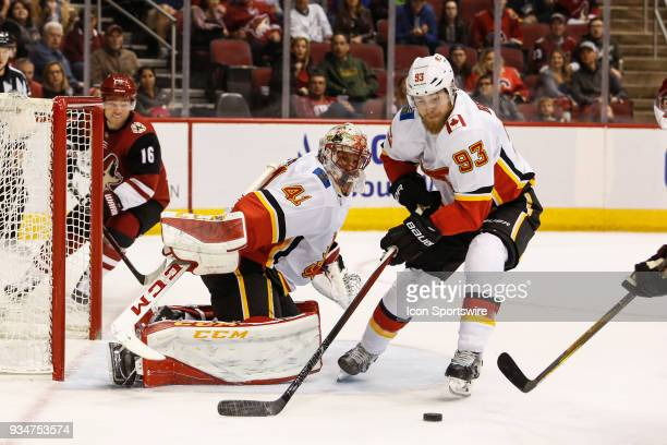 Calgary Flames center Sam Bennett tries to control the puck after a save by Calgary Flames goaltender Mike Smith during the NHL hockey game between...