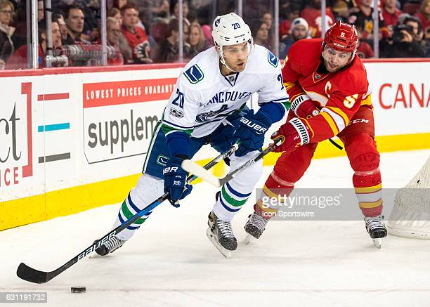 Calgary Flames Defenceman Mark Giordano tries to steal the puck from Vancouver Canucks Center Brandon Sutter during a game between the Calgary Flames...