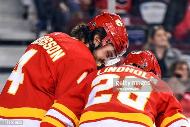 Calgary Flames Defenceman Rasmus Andersson leans in to talk strategy with Right Wing Elias Lindholm before a faceoff during the first period of an...