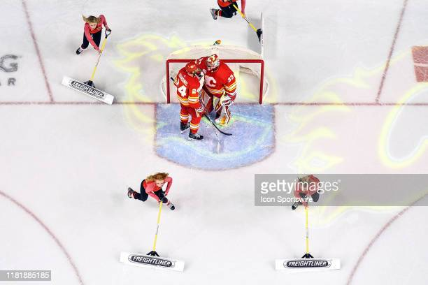 Calgary Flames Defenceman Travis Hamonic and Goalie David Rittich celebrate a goal while the Calgary Flames ice girls clean the ice during an NHL...