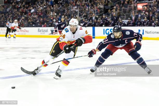 Calgary Flames defenseman Travis Hamonic and Columbus Blue Jackets left wing Nick Foligno battle for control of the puck during the second period in...