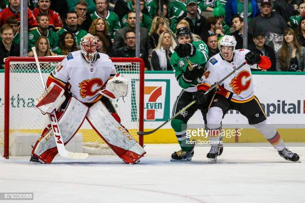 Calgary Flames defenseman Travis Hamonic and Dallas Stars left wing Antoine Roussel battle for position in front of Calgary Flames goalie Mike Smith...