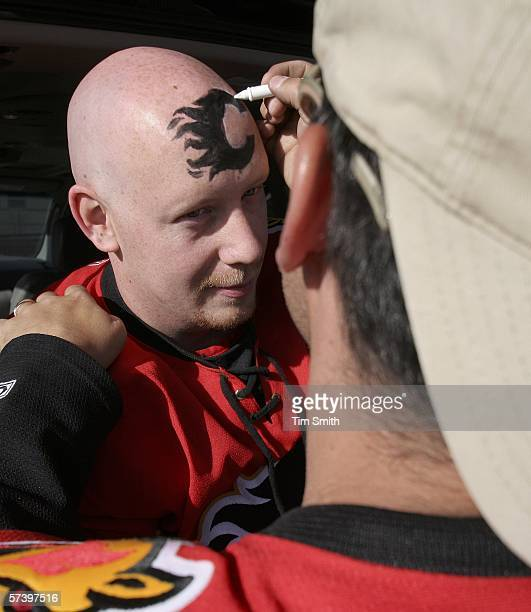 Calgary Flames fan Brad Duggan has the Flames logo painted on his forehead by friend Jason Johnson during a pregame party in the parking lot of the...
