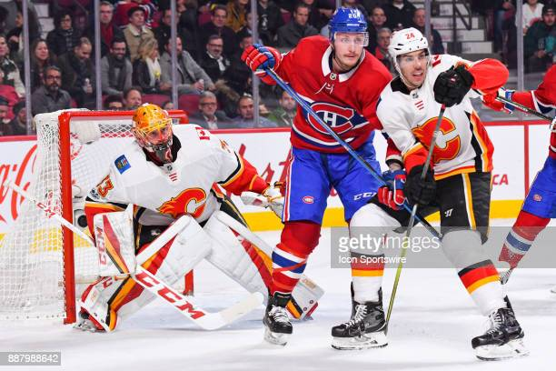 Calgary Flames Goalie David Rittich tries to look around Montreal Canadiens Left Wing Nicolas Deslauriers and Calgary Flames Defenceman Travis...