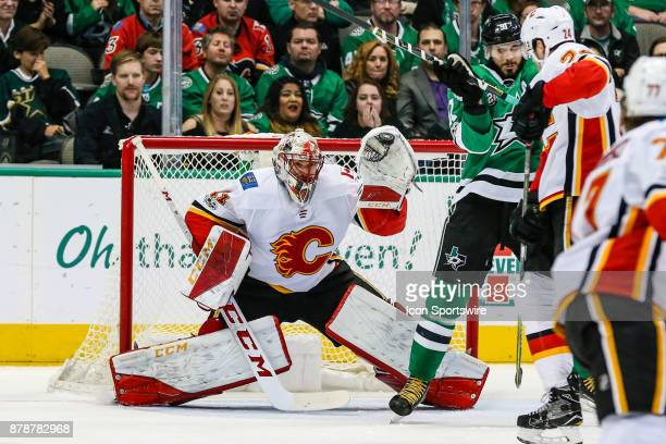 Calgary Flames goalie Mike Smith catches the puck in his glove hand as Dallas Stars center Tyler Seguin and Calgary Flames defenseman Travis Hamonic...