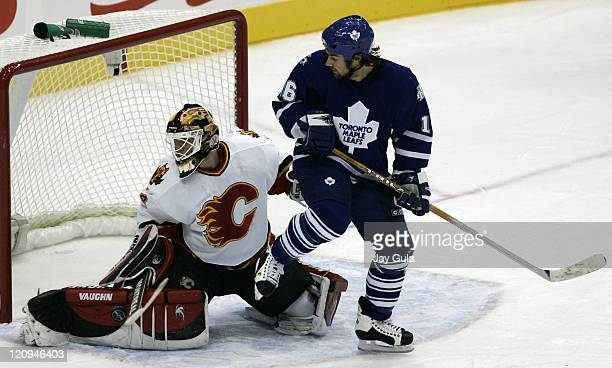 Calgary Flames goaltender Mikka Kiprusoff makes a save as Toronto Maple Leaf forward Darcy Tucker provides a screen in action at the Air Canada...