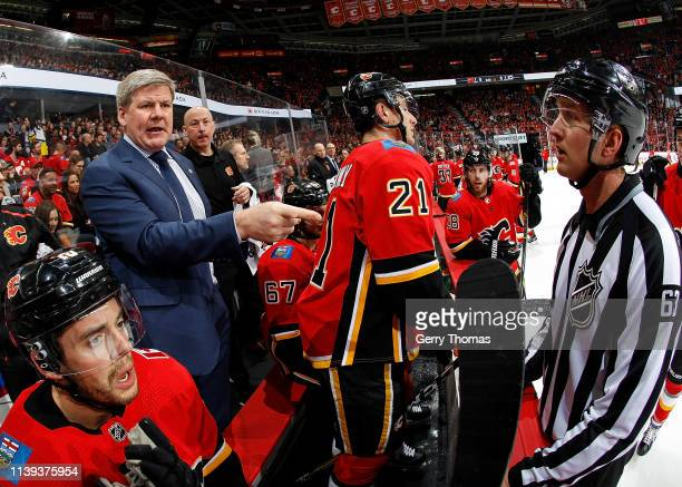 Calgary Flames head coach Bill Peters talks to an official during an NHL game against the Dallas Stars on March 27 2019 at the Scotiabank Saddledome...