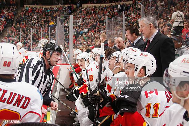 Calgary Flames head coach Bob Hartley and linesman Don Henderson talk during the game against the Minnesota Wild on March 27 2015 at the Xcel Energy...