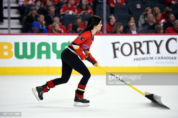 Calgary Flames ice girl cleans the ice between whistles during the first period of an NHL game where the Calgary Flames hosted the Minnesota Wild on...