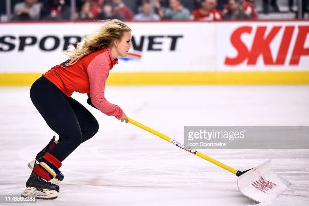 Calgary Flames ice girl cleans the ice during the first period of an NHL game where the Calgary Flames hosted the Detroit Red Wings on October 17 at...