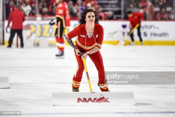 Calgary Flames ice girl cleans the ice during the first period of an NHL game where the Calgary Flames hosted the Chicago Blackhawks on February 15...