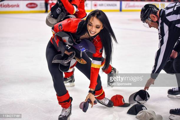Calgary Flames ice girl picks up hats after Calgary Flames Center Sean Monahan scores a goal during the third period of an NHL game where the Calgary...