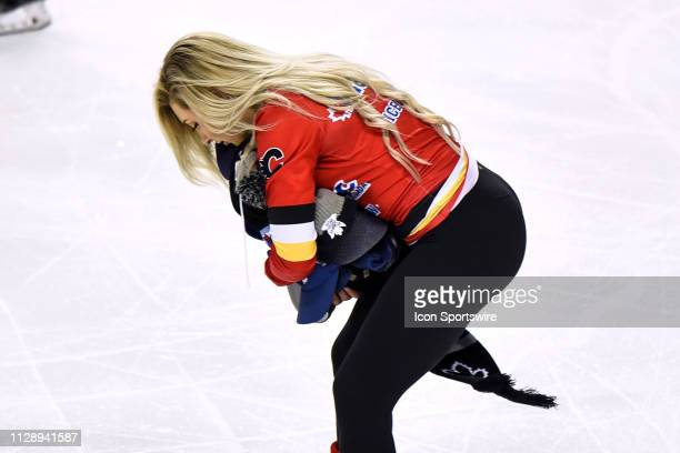 Calgary Flames ice girl pucks up hats after Toronto Maple Leafs Left Wing Tyler Ennis scores a hat trick during the third period of an NHL game where...