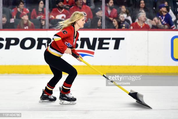 Calgary Flames ice girl shovels the snow off the ice during the first period of an NHL game where the Calgary Flames hosted the New York Rangers on...