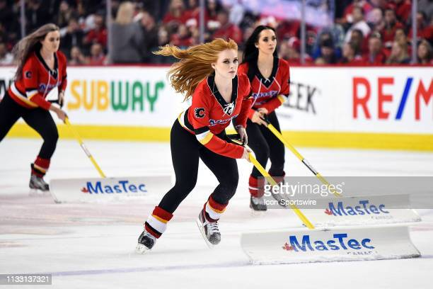 Calgary Flames ice girls clean the ice between plays during the first period of an NHL game where the Calgary Flames hosted the Ottawa Senators on...