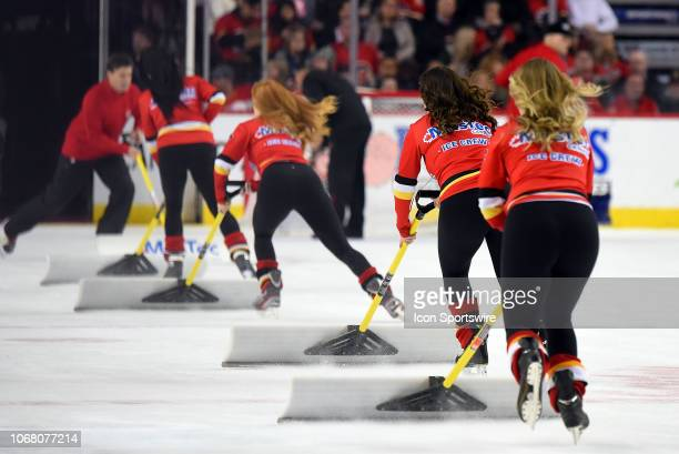 Calgary Flames ice girls clean the ice between whistles during the first period of an NHL game where the Calgary Flames hosted the Los Angeles Kings...