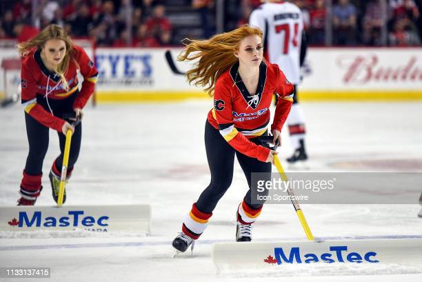 Calgary Flames ice girls clean the ice between whistles during the third period of an NHL game where the Calgary Flames hosted the Ottawa Senators on...