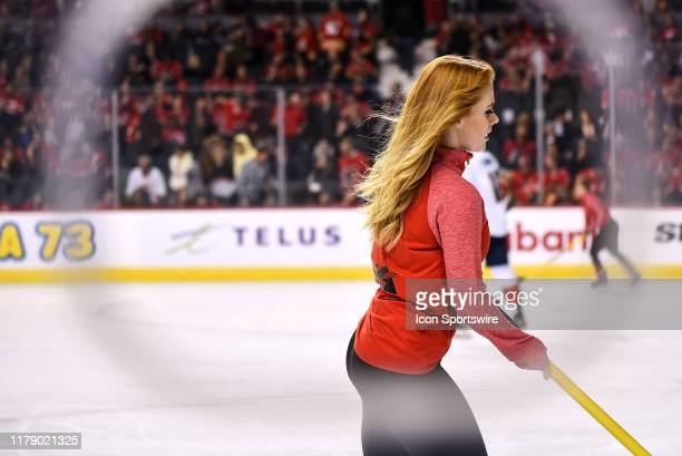 Calgary Flames ice girls clean the ice between whistles during the second period of an NHL game where the Calgary Flames hosted the Florida Panthers...