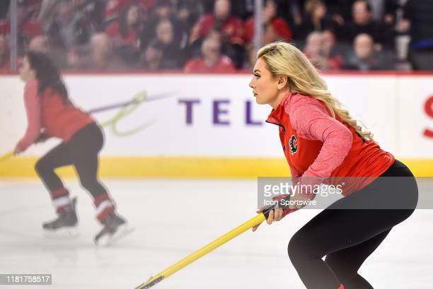 Calgary Flames ice girls clean the ice during the first period of an NHL game where the Calgary Flames hosted the New Jersey Devils on November 7 at...