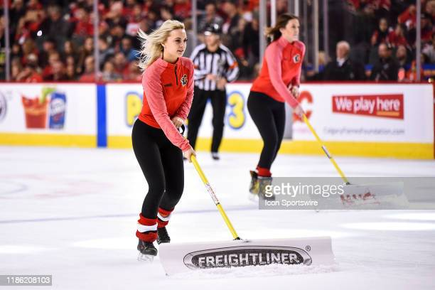 Calgary Flames ice girls clean the ice during the first period of an NHL game where the Calgary Flames hosted the Ottawa Senators on November 30 at...