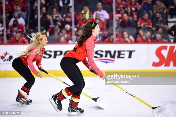 Calgary Flames ice girls clean the ice during the first period of an NHL game where the Calgary Flames hosted the Montreal Canadiens on December 19...
