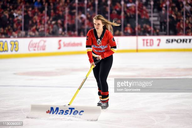 Calgary Flames ice girls scrape the snow off the ice between whistles during the first period of an NHL game where the Calgary Flames hosted the...