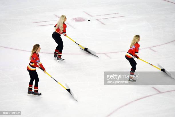 Calgary Flames ice girls shovels the snow during the third period of an NHL game where the Calgary Flames hosted the Vegas Golden Knights on November...
