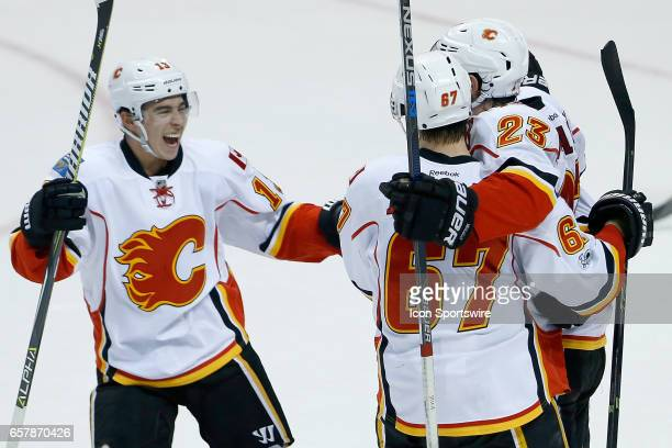 Calgary Flames left wing Johnny Gaudreau right wing Michael Frolik celebrate with center Sean Monahan after Monahan scored the winning goal during...
